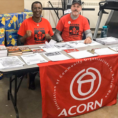 Bob Murphy sitting with an ACORN member at  an information table